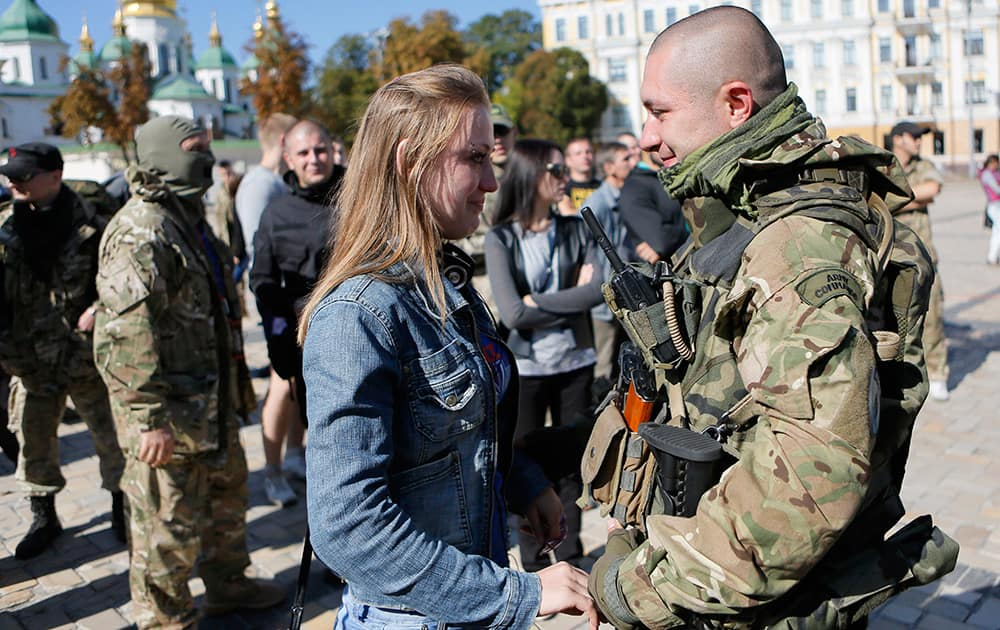 A fighter from the Azov volunteer battalion talks to his girlfriend after returning from rotation at the front line in Kiev, Ukraine.