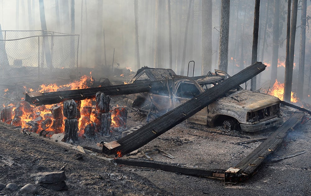 A burned truck and smoldering ruins is all that is left of a garage near a house that burned on Cedar Drive in Oakhurst, Calif., as two raging wildfires in the state forced hundreds of people to evacuate their homes.
