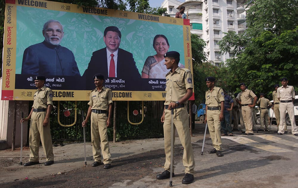 Policemen stand next to a welcome hoarding being erected ahead of an anticipated visit by Chinese President Xi Jinping as they review security arrangements in Ahmedabad.