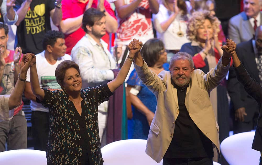 Brazil's President Dilma Rousseff, of the Workers Party (PT), running for re-election, left, and former President Luiz Inacio Lula da Silva greet supporters during a gathering with artists in Rio de Janeiro, Brazil.