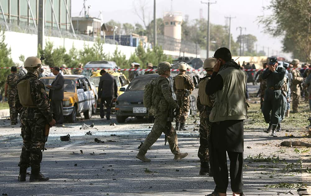 NATO and Afghan security forces inspect the site of a suicide attack in Kabul, Afghanistan. A Taliban suicide car bomber attacked a foreign motorcade just a couple hundred yards (meters) from the U.S. Embassy, unleashing a blast that injured at least 13 people and rattled nearby neighborhoods, police officials said.