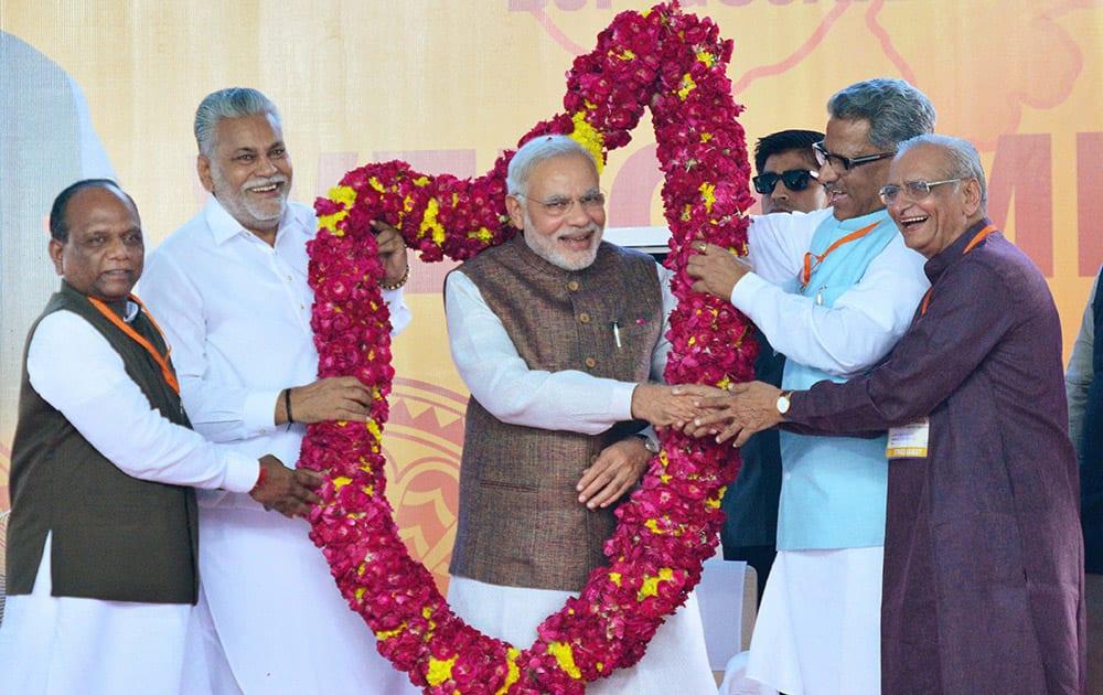 Prime Minister Narendra Modi is garlanded on his arrival at Sardar Patel International Airport in Ahmedabad.