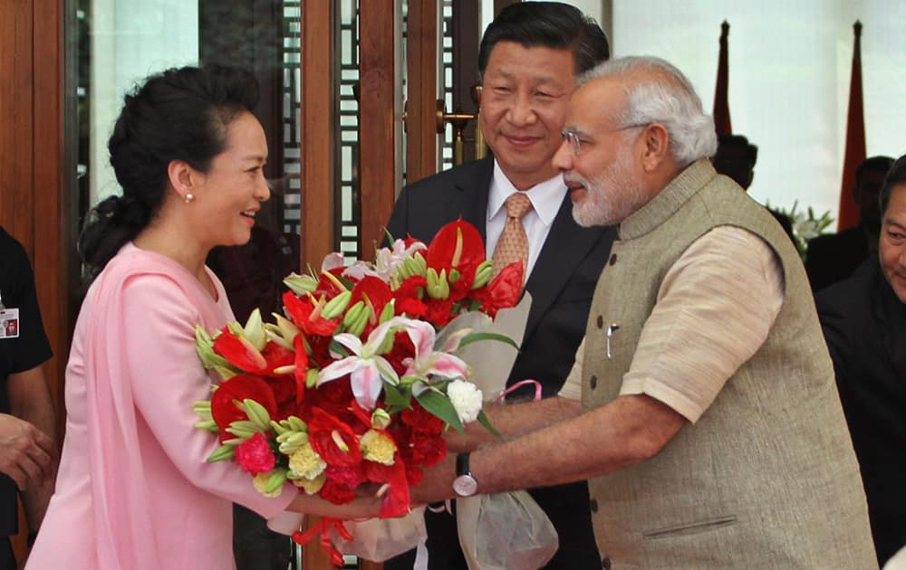 Prime Minister Narendra Modi, welcomes Chinese President Xi Jinping and Xi's wife Peng Liyuan upon arrival at a hotel in Ahmadabad.