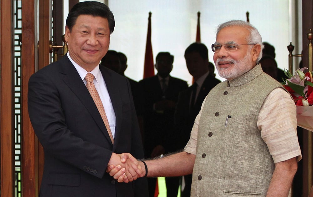 Prime Minister Narendra Modi poses with Chinese President Xi Jinping as he welcomes him upon his arrival at a hotel in Ahmadabad.