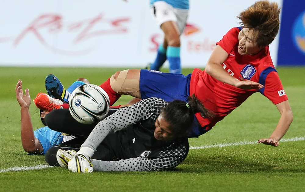 South Korea's Younga Yoo, right, is tackled by India's goalkeeper Aditi Chauhan, foreground, during their women's first round group A soccer match at the 17th Asian Games in Incheon, South Korea.