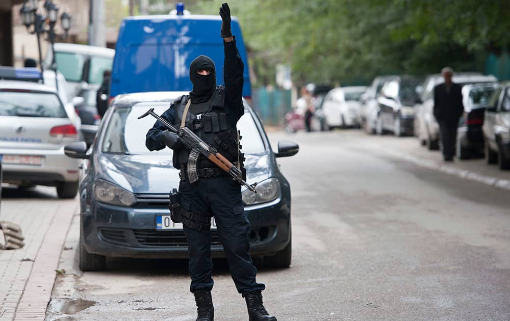 A Kosovo police officer gestures outside the apartment of the vice-president of the radical Islamic political party (LISBA) Fuad Ramiqi, during a police raid, in Pristina.