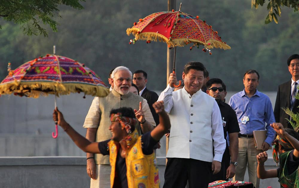 Chinese President Xi Jinping and Indian Prime Minister Narendra Modi watch a cultural performance as they walk on the Sabarmati River front in Ahmadabad.