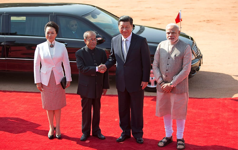 Indian President Pranab Mukherjee, second left, shakes hand with visiting Chinese President Xi Jinping, as Indian Prime Minister Narendra Modi and Xi's wife Peng Liyuan stand beside them in New Delhi.