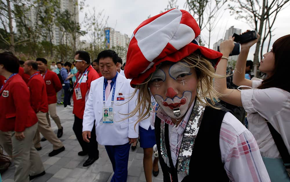 A volunteer with his face painted cheers delegations' arrival for the welcoming ceremony at the Flag Plaza of the Athlete's Village for the 2014 Incheon Asian Games in Incheon, west of Seoul, South Korea.