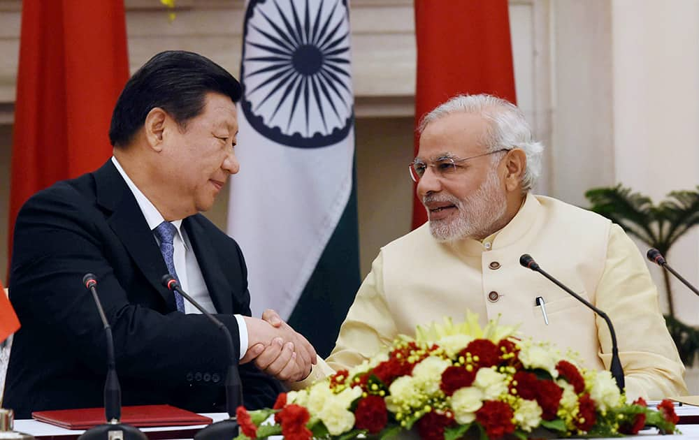 Prime Minister Narendra Modi and Chinese President Xi Jinping shake hands after the joint statement following the agreement signing ceremony at Hyderabad House in New Delhi.