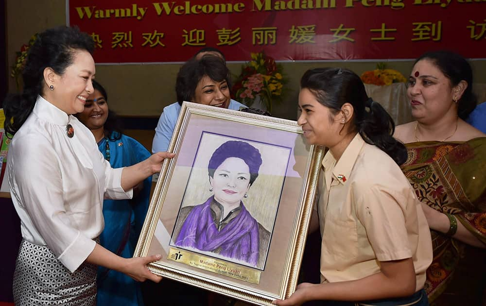 Chinas first lady Peng Liyuan is presented with a portrait of her by a student during her visit to the Tagore International School in New Delhi.