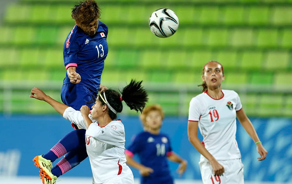 Japan's Yuika Sugasawa leaps over Jordan's Alaa Fouad Daowd Abu Kasheh to score a goal as Ayah Faisal Ayed Al Majali, looks on during their match at the 17th Asian Games in Incheon, South Korea.