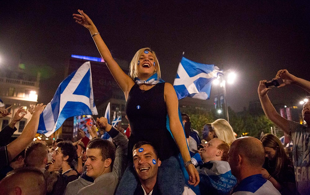 A man carries a woman on his shoulders as supporters of the Yes campaign in the Scottish independence referendum shout and cheer as they await the result after the polls closed, in George Square, Glasgow, Scotland.