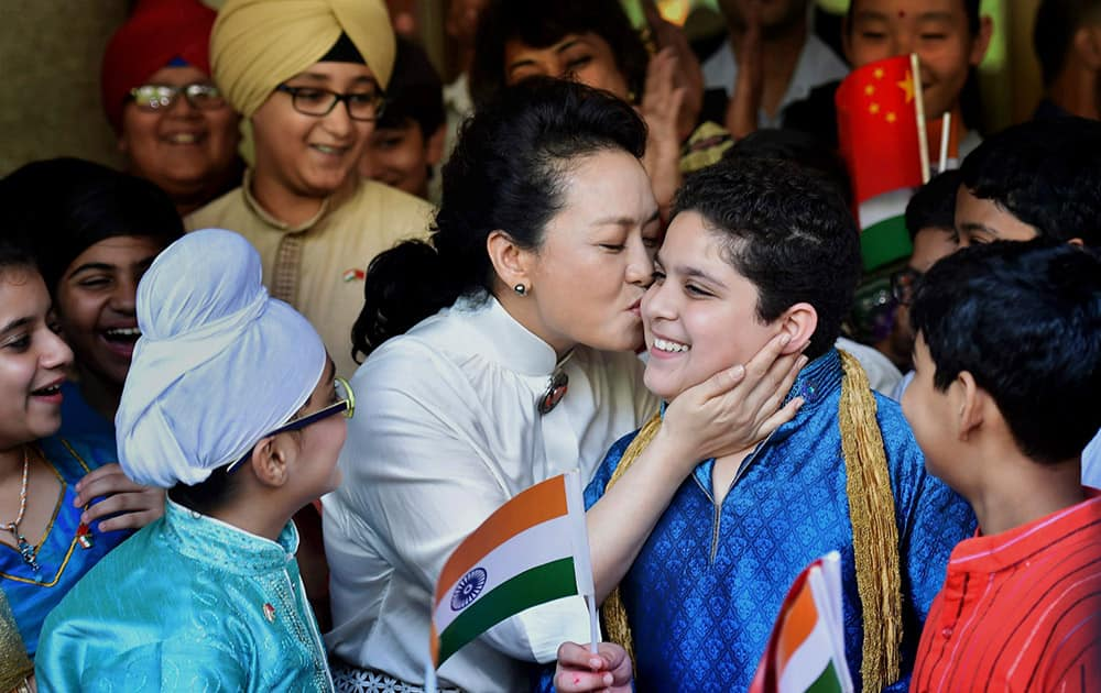 Visiting Chinese President Xi Jinping's wife Peng Liyuan kisses a student during a visit to the Tagore International School in New Delhi.