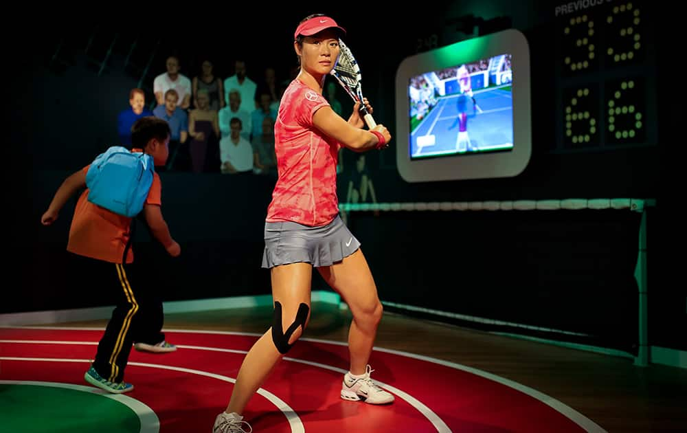 A student plays with a motion-controlled tennis games near a wax figure of Chinese tennis player Li Na on display at the Madame Tussauds Museum in Beijing.