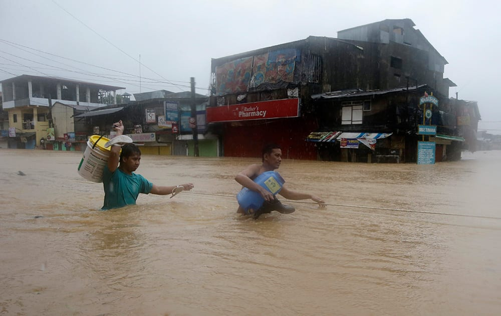Residents make their way through deep floodwaters after heavy monsoon rains spawned by tropical storm Fung-Wong flooded Marikina city, east of Manila.
