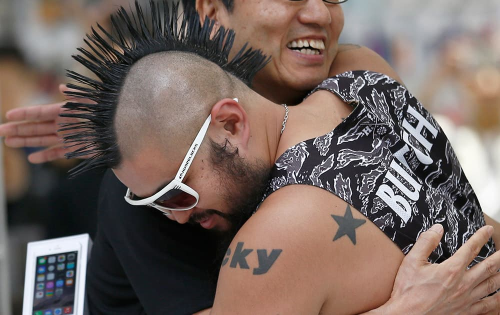 Ken Miyauchi, left, vice president of Softbank, Japanese mobile phone company hugs the first customer of iPhone 6 during a ceremony to mark the first day of sales of the new Apple iPhone 6 and 6 Plus at a store in Tokyo.