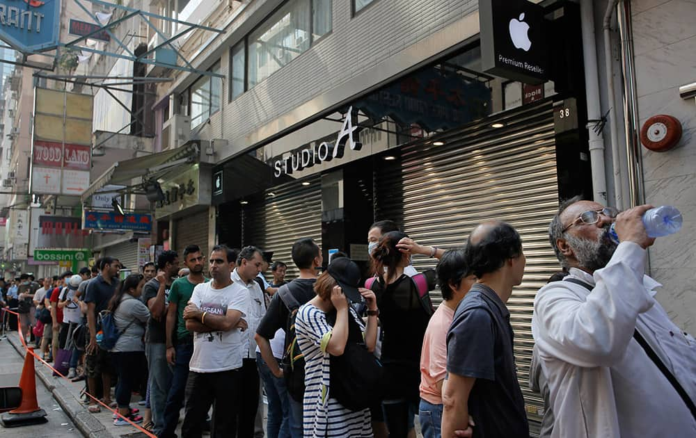 People wait to buy the new Apple iPhone 6 and 6 Plus devices, outside an Apple premium reseller store in Hong Kong. The iPhone 6 and 6 Plus were released on Friday in Hong Kong.