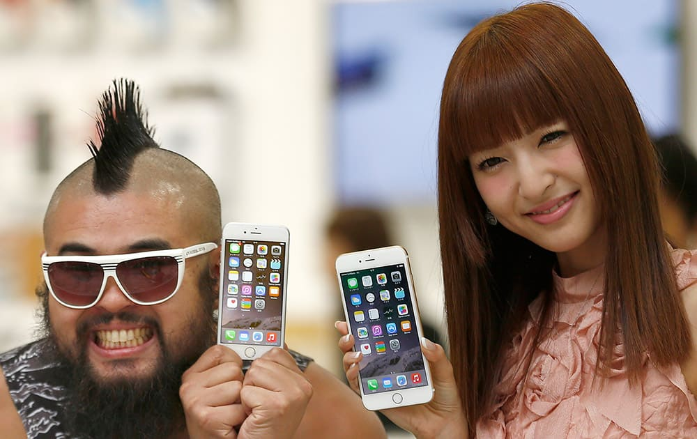 A customer and actress Sayaka Kanda pose for photographers during a ceremony to mark the first day of sales of the latest iPhone 6 and 6 Plus at a store in Tokyo .