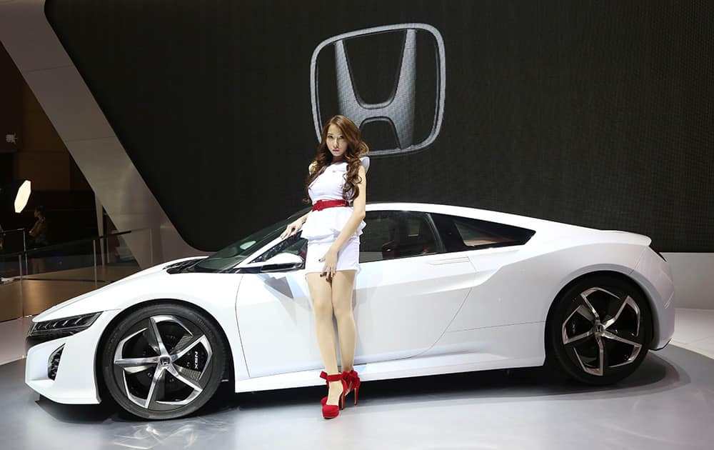 A model stands beside concept vehicle of Honda NSX during the Indonesia International Motorshow in Jakarta, Indonesia.