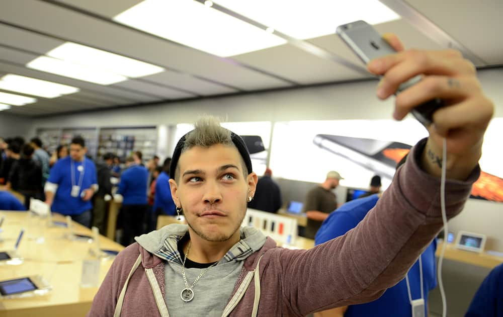 Dani Winters poses as he takes a selfie with a new iPhone at the iPhone 6 launch at the Eaton Centre Apple Store, in Toronto.