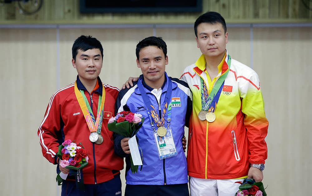 Winner India's Jitu Rai, center, silver medalist Vietnam's Nguyen Hoang Phuong, left, and bronze medalist China's Wang Zhiwei pose for the media during the medal ceremony for the 50m Pistol Men at the Ongnyeon International Shooting Range for the 17th Asian Games in Incheon, South Korea.