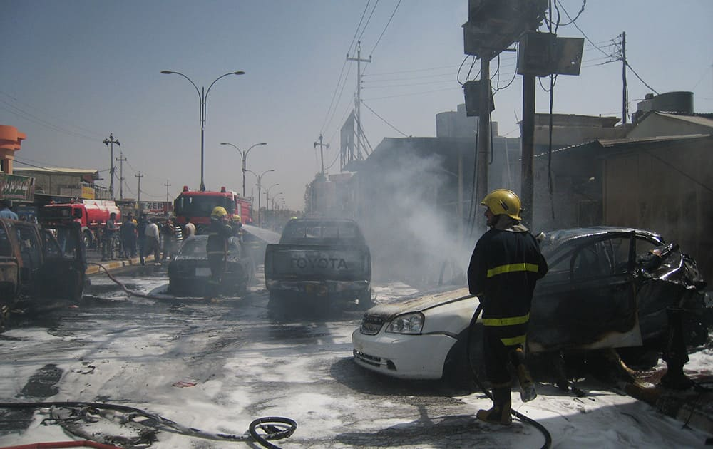 Iraqi firefighters put out fires ignited by a motorcycle bomb attack in Kirkuk, 290 kilometers (180 miles) north of Baghdad,.