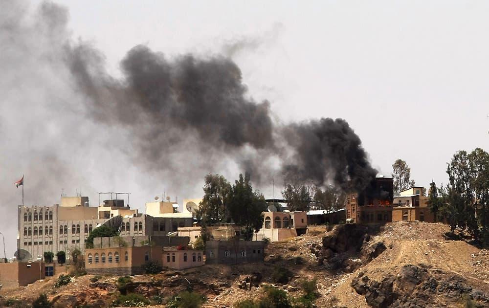Smokes rises from near the Yemeni Government TV building, background, during clashes between Sunni militiamen and Hawthi Shiite rebels in Sanaa, Yemen.