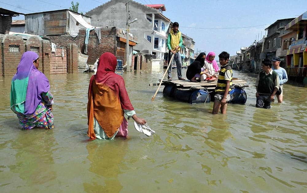 People shifting from a flooded locality on the outskirts of Srinagar.