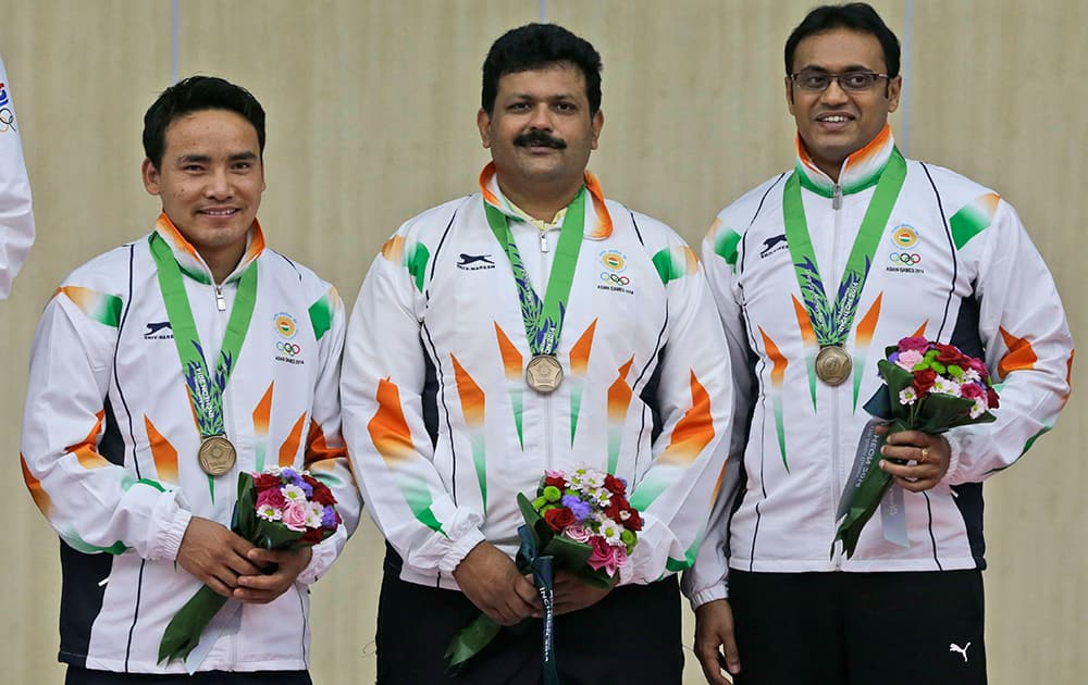 Bronze medalist, from left to right, Jitu Rai, Samaresh Jung and Prakas Papanna Nanjappa of India pose for photographers dduring the victory ceremony for the Men's 10m Air Pistol Team shooting competition at the 17th Asian Games at Ongnyeon International Shooting Range in Incheon, South Korea.