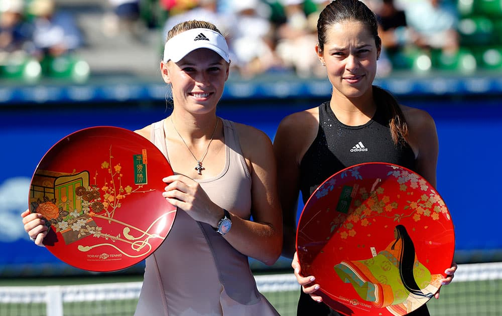 Ana Ivanovic of Serbia, right, and Caroline Wozniacki of Denmark pose for photographers after Ivanovic beat Wozniacki in their final to win the of the Pan Pacific Open Tennis tournament in Tokyo.