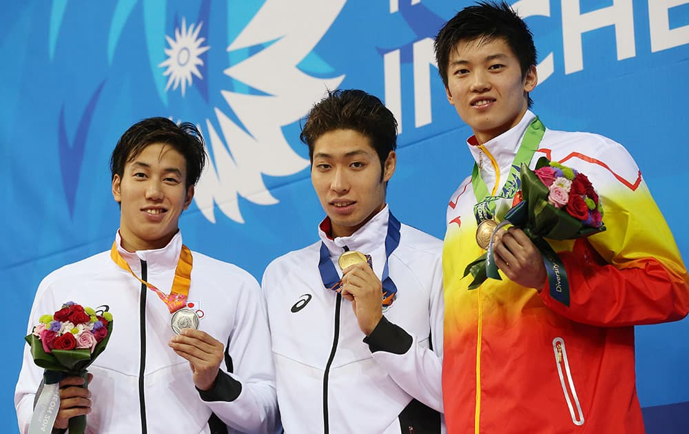 Men's 200-meter individual medley medalists from left, Japan's Hiromasa Fujimori, silver, and his compatriot Kosuke Hagino, gold, and bronze China's Wang Shun pose for a photo on the podium at the 17th Asian Games in Incheon, South Korea.