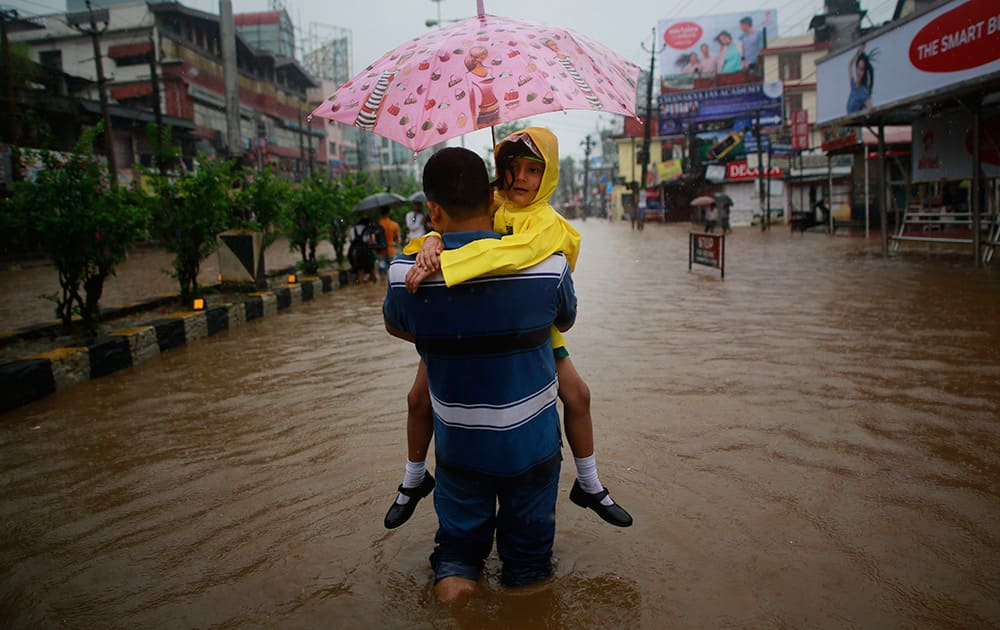 A man carrying his daughter wades through floodwaters in Guwahati, Assam. Officials say relentless rains in parts of northeastern India have triggered landslides and flash floods, killing at least seven people.