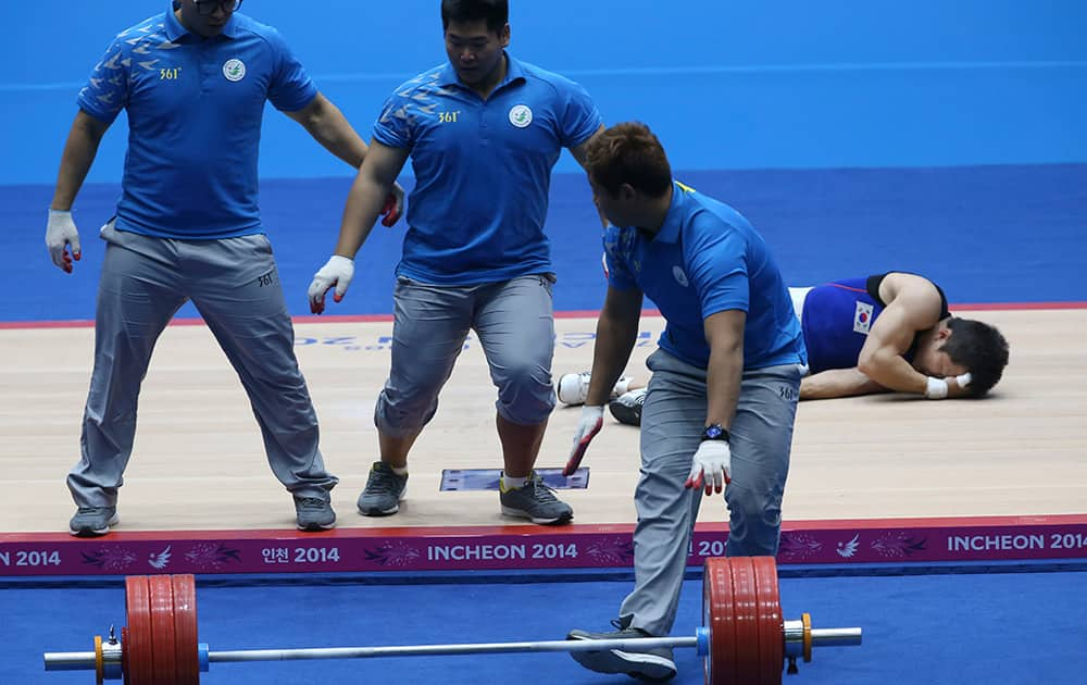 Competition officials rush to remove the barbell as South Korea's Won Jeong-sik suffers an injury during the men's 69kg weightlifting competition at the 17th Asian Games in Incheon, Korea.