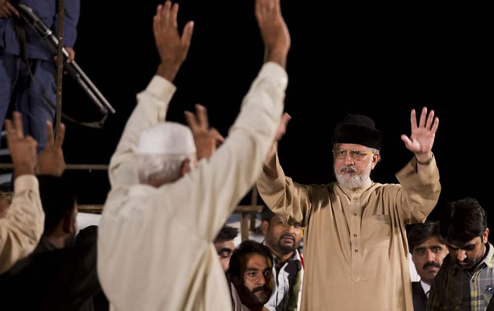 Pakistan's fiery Muslim cleric Tahir-ul-Qadri, left, greets his supporters, camped in the vicinity of the parliament building in Islamabad, Pakistan.