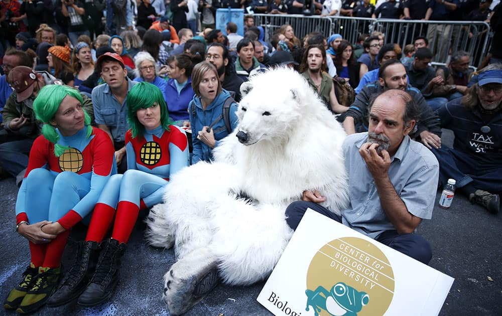 Protesters, including one dressed as a polar bear, sit at the intersection of Wall St. and Broad St. in New York.