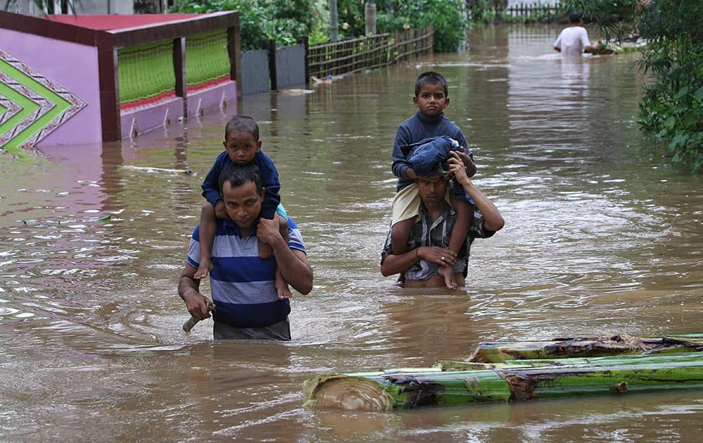 Indian villagers carry their children on their shoulders and wade through flood waters at the Chaygaon village in Kamrup district of northeastern Assam state, India.