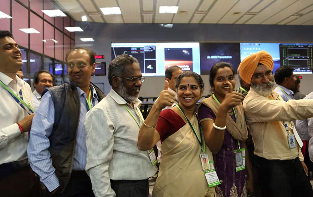 Indian Space Research Organisation scientists and officials cheer as they celebrate the success of Mars Orbiter Mission at their Telemetry, Tracking and Command Network complex in Bangalore.