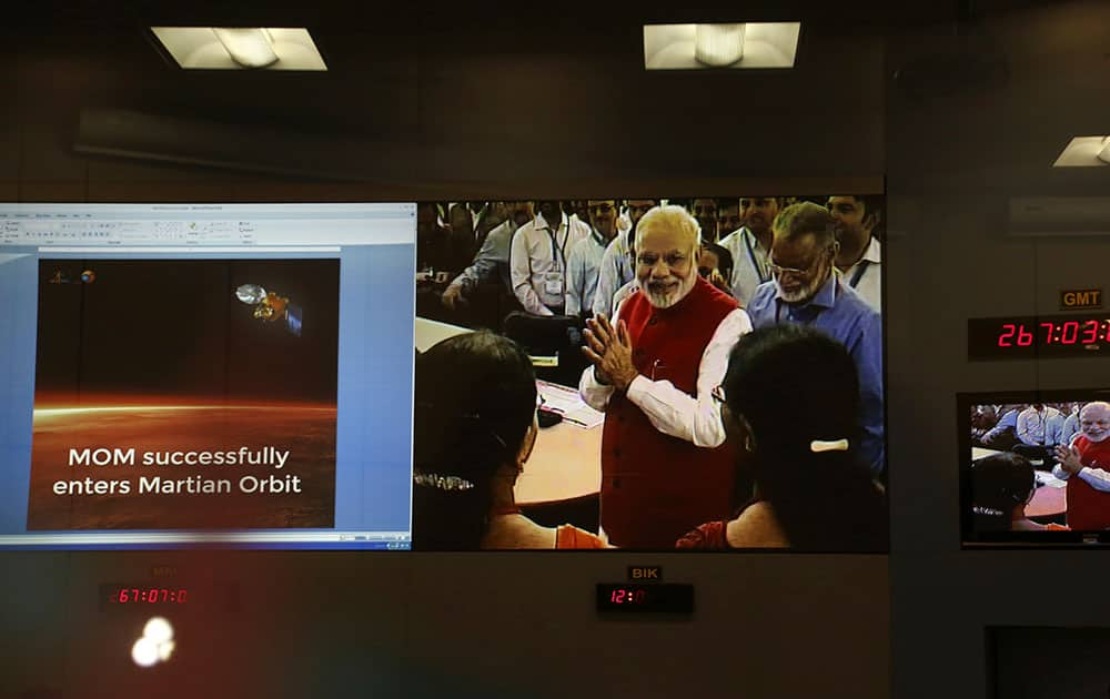 Screens show Indian Prime Minister Narendra Modi greeting Indian Space Research Organisation scientists and other officials after the success of Mars Orbiter Mission at their Telemetry, Tracking and Command Network complex in Bangalore.