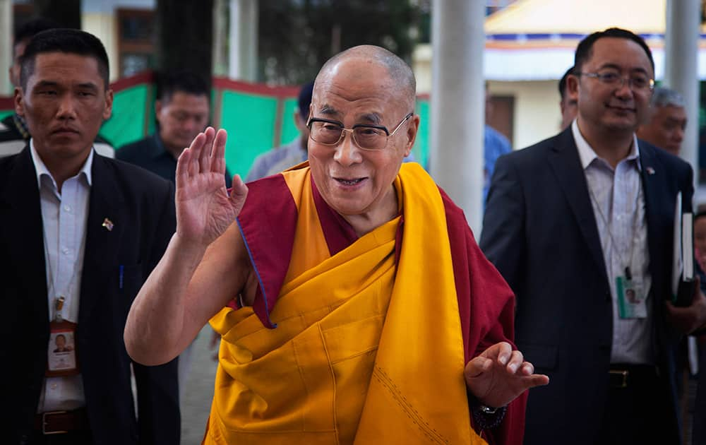 Tibetan spiritual leader the Dalai Lama, center, greets devotees as he arrives at the Tsuglakhang temple for a religious talk in Dharmsala.