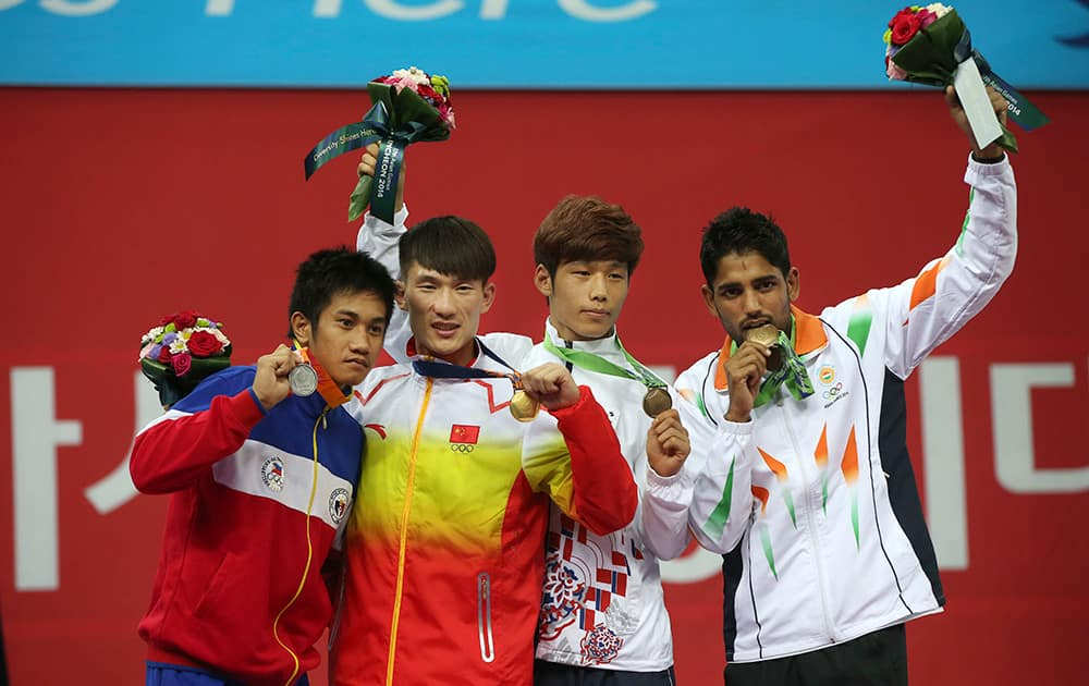 Medalists of the men's 60kg Wushu Sanda competition standing left to right; Philippines Jean Claude Saclag, silver, China's Kong Hongxing, gold, South Korea's Kang Yeong-sik, bronze, and India's Narender Grewal display their medals at the 17th Asian Games in Incheon, South Korea.