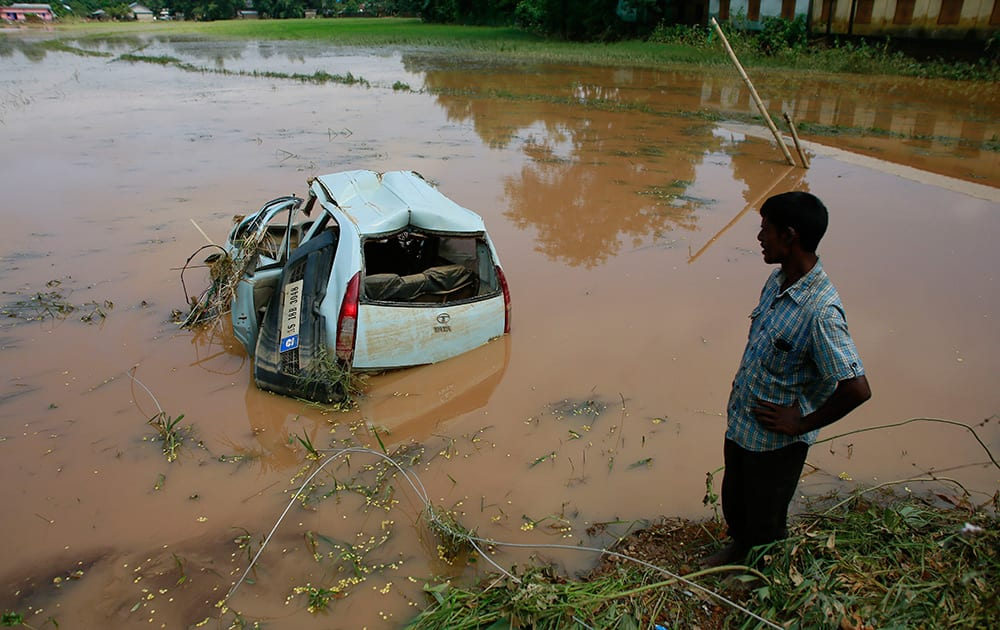 A man looks a car that got washed away in the flash floods as it lies damaged in a paddy field in Krishnai village in Goalpara district of northeastern Assam state.