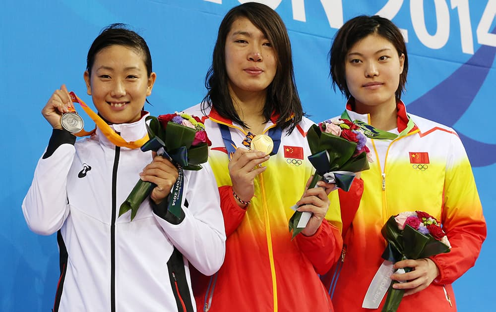 Gold medalist China's Shen Duo, centre, stands with silver medalist Japan's Chihiro Igrarashi, left, compatriot and bronze medalist China's Tang Yi , right, after winning the women's 200-meter freestyle swimming final at the 17th Asian Games in Incheon, South Korea