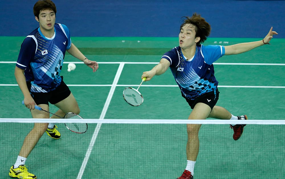 South Korea's Kim Sa-rang, right, and Kim Gi-jung returns the shuttlecock against China's Cai Yu and Fu Haifeng during their Men's Team badminton final match at the 17th Asian Games in Incheon, South Korea