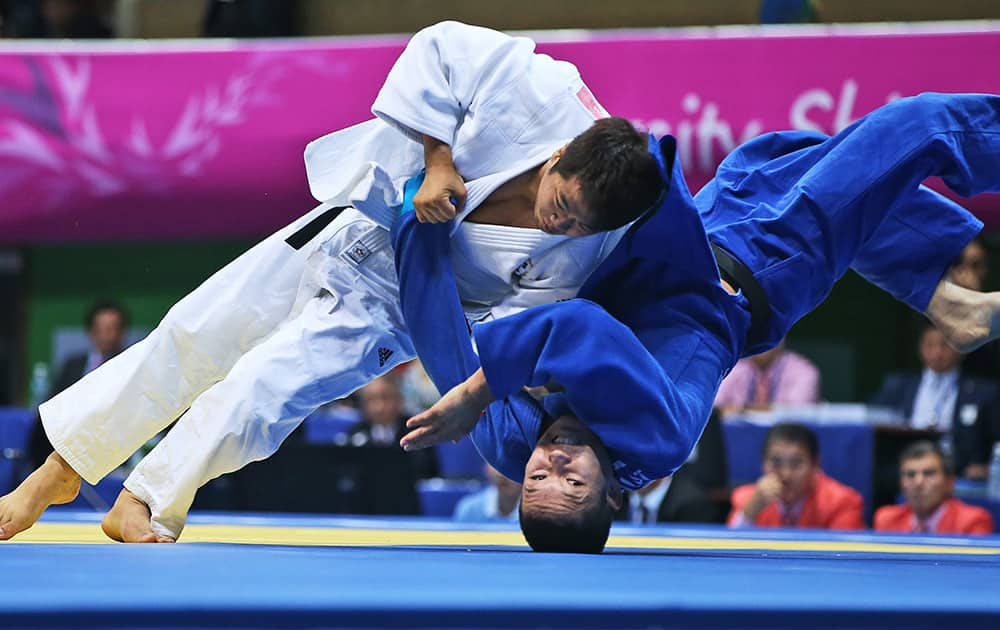 South Korea's Lee Kyu-won, in white, competes against Kazakhstan's Timur Bolat during the men's Judo team contest for gold medal at the 17th Asian Games Tuesday, Sept. 23, 2014 in Incheon.