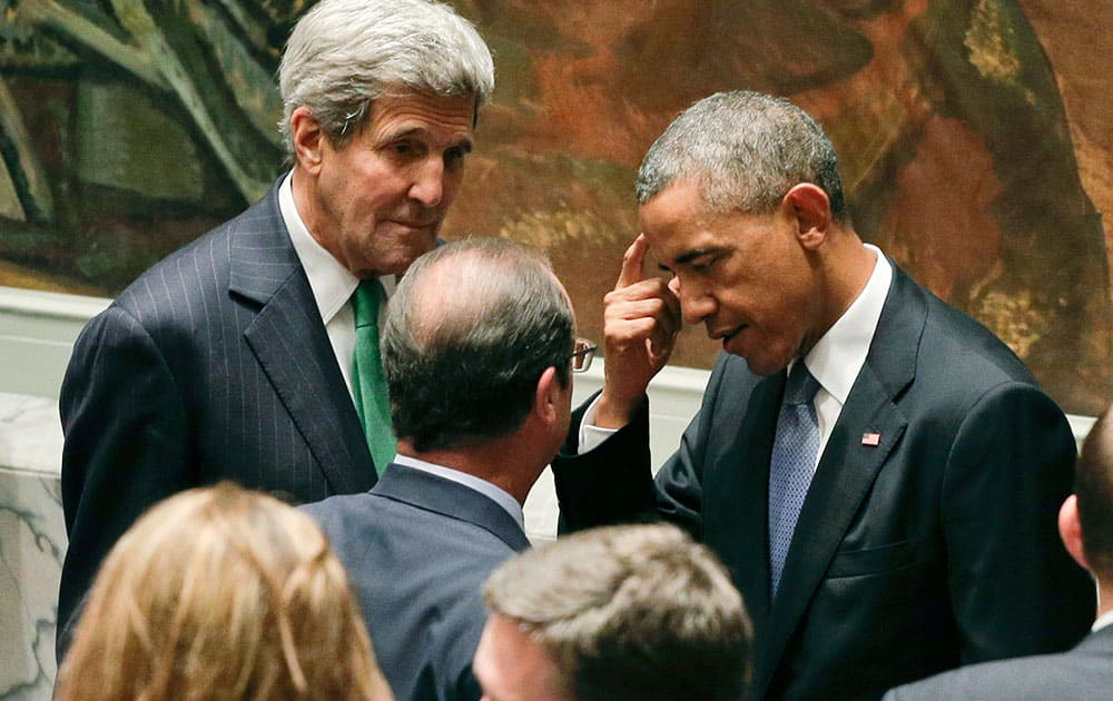 President Barack Obama, right, and Secretary of State John Kerry, left, talk with French president Nicolas Hollande before a UN Security Council meeting, at the United Nations. Members of the Security Council were expected to adopt a resolution that would require all countries to prevent the recruitment and transport of would-be foreign fighters preparing to join terrorist groups such as the Islamic State group.