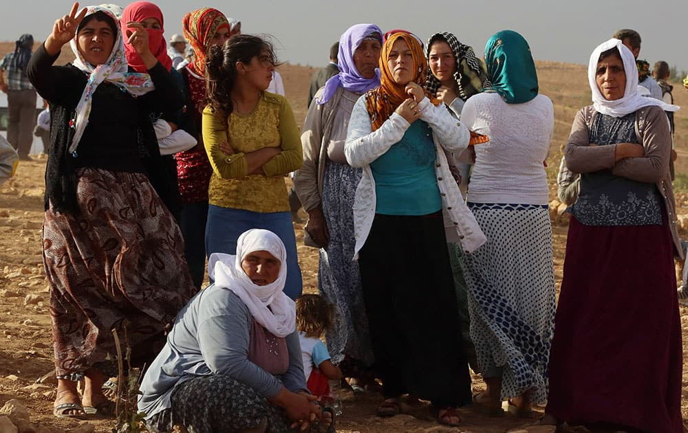 Turkish Kurds shout slogans in support of Syrian Kurdish fighters in the other side of the border near Suruc, Turkey.