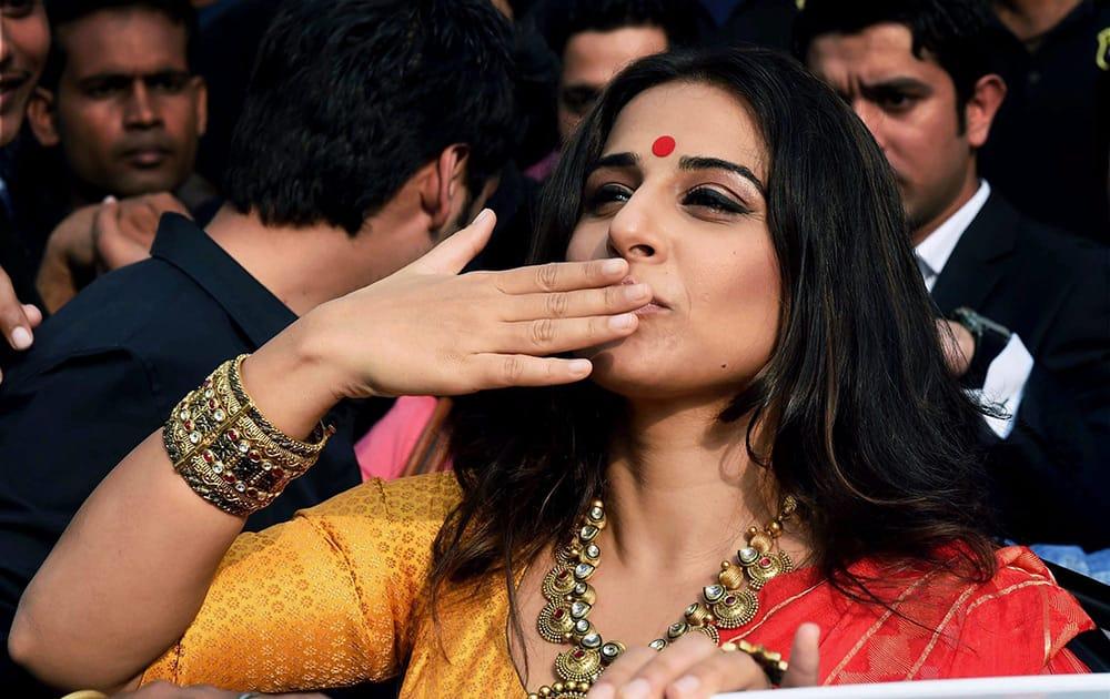 Vidya Balan gestures towards fans during a promotional event in Kolkata.