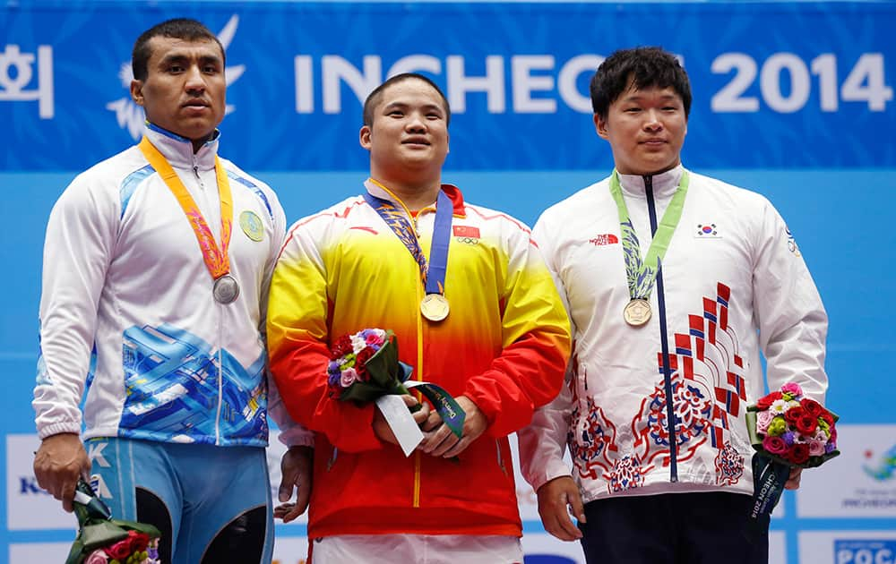 From left, silver medal winner Kazakhstan's Almas Uteshov, gold medal winner China's Liu Hao and bronze medal winner South Korea's Lee Chang-ho celebrate after winning the men's 94kg weightlifting competition at the 17th Asian Games in Incheon, South Korea.