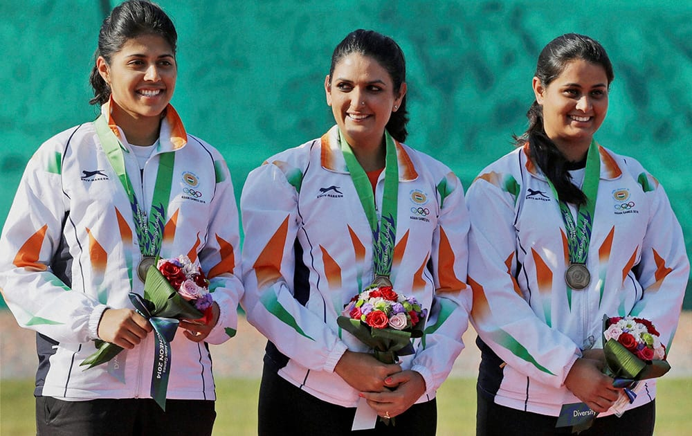 Bronze medalist from left to right, Varman Varsha, Shagun Chowdary and Shreyasi Singh pose for photographers during the medal ceremony for the Womens Double Trap Team shooting competition at the 17th Asian Games in Incheon, South Korea.